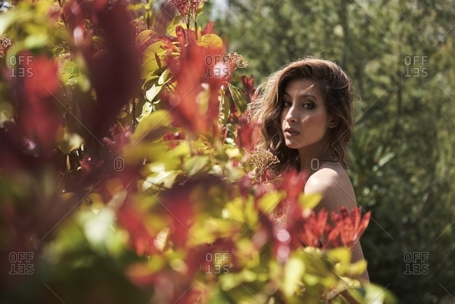 Side view of gentle female with long hair and in red elegant dress standing in summer garden and looking at camera