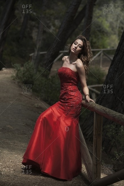 Side view of graceful female wearing long red dress leaning on wooden fence in forest and enjoying nature with closed eyes