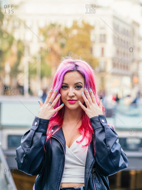 Optimistic confident millennial female with dyed pink hair wearing leather jacket looking at camera and smiling while standing against blurred urban background