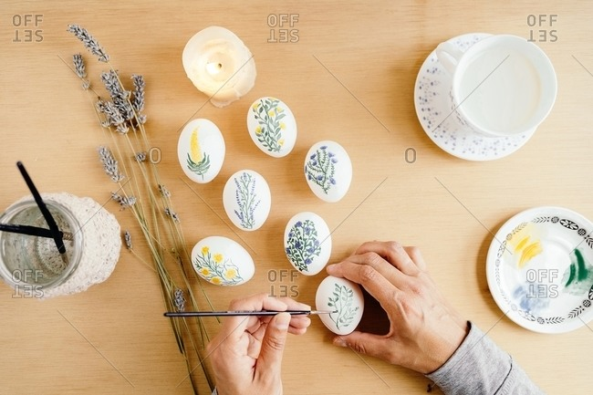 From above of crop unrecognizable person with paintbrush painting flowers on white eggs while preparing for Easter celebration at home