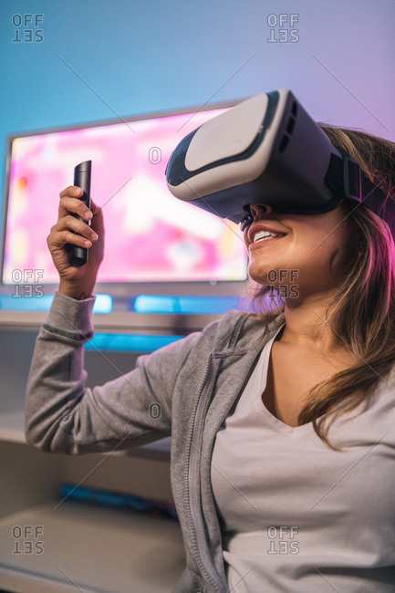 Excited female gamer playing video game in virtual reality headset while sitting in room with neon light