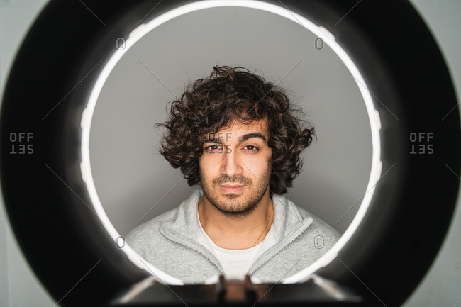 Serious young casually dressed bearded ethnic male with curly hair looking at camera through hole of ring lamp