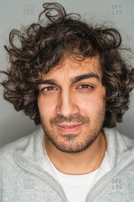 Handsome young unshaven ethnic male with curly hair looking seriously at camera against gray background