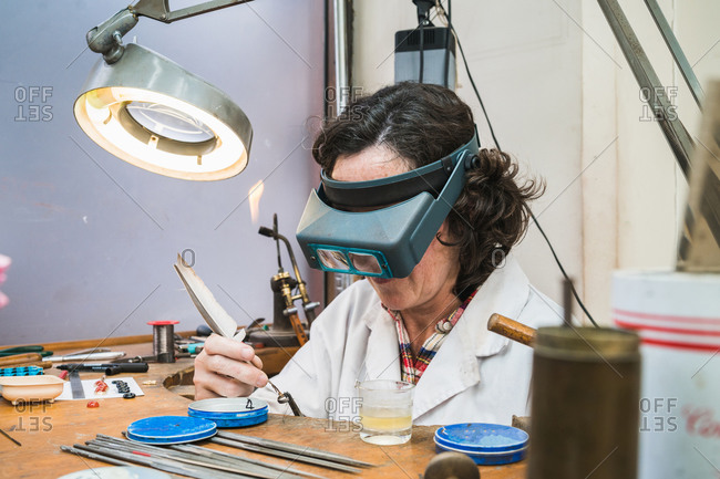 Side view of concentrated mature female master in glasses using ring sizer while creating jewelry in workshop
