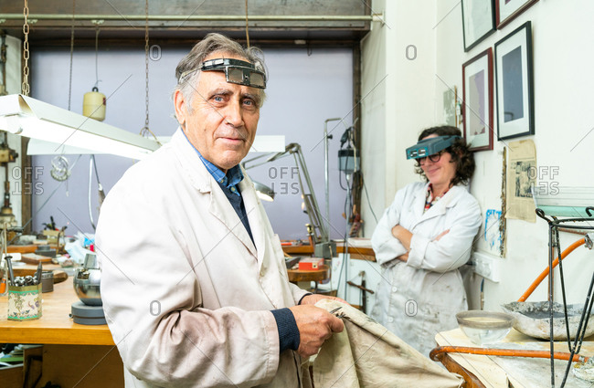 Side view of mature gray haired professional male jeweler in work wear and with glasses on forehead looking at camera while working with female colleague in workshop