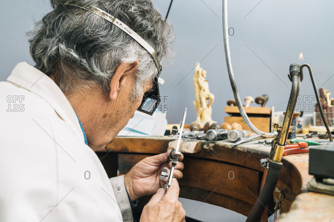 Side view of concentrated skilled mature male master in glasses using ring sizer while creating jewelry in workshop
