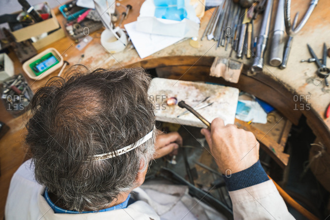 From above of focused skilled mature male master in glasses using hammer and chisel while working with gemstone in jewelry workshop