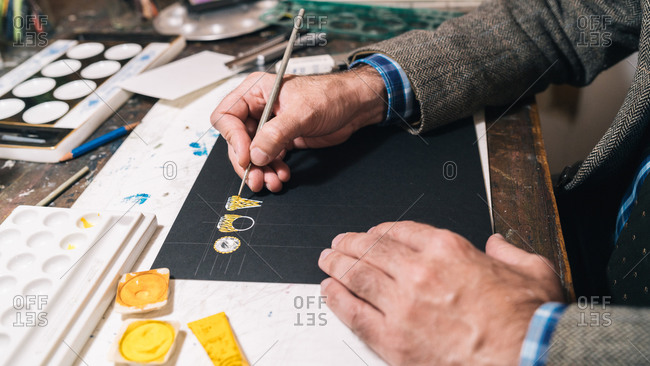 Side view crop anonymous male artist creating jewelry ring design and coloring sketch with yellow paint while working in professional workshop