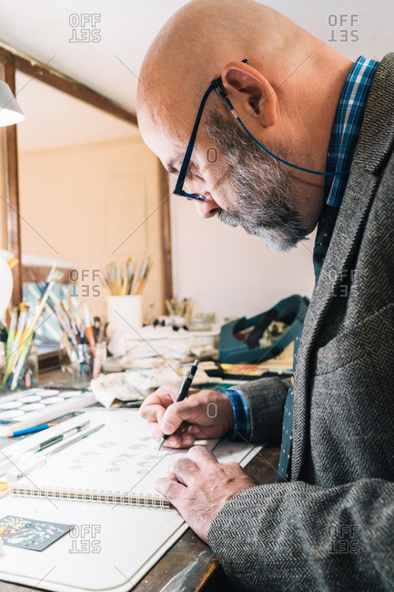 Side view of focused creative mature male designer working on jewelry designs and drawing sketches while sitting at table with professional supplies in workplace
