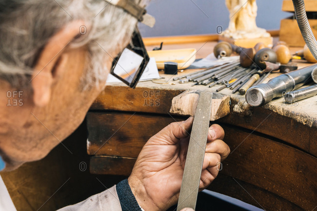 Side view of crop skilled mature craftsman in special glasses using polishing hand tool while creating jewelry accessory in workshop