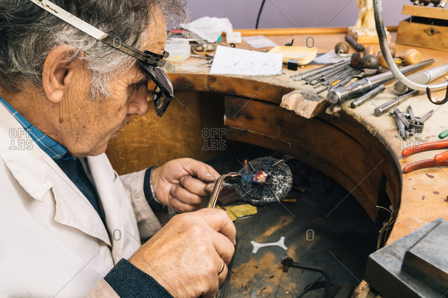 High angle side view of skilled mature male master in glasses using soldering iron while working at workbench with professional instruments in jewelry workshop