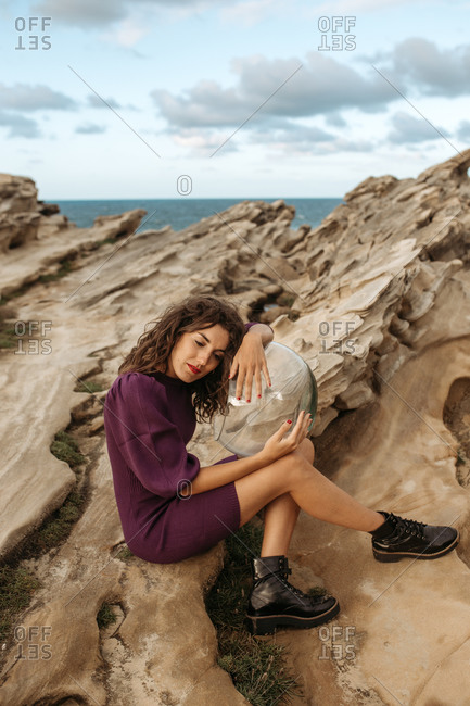 Side view of female sitting on rocky ground and hugging glass cosmonaut helmet while pretending being spaceman