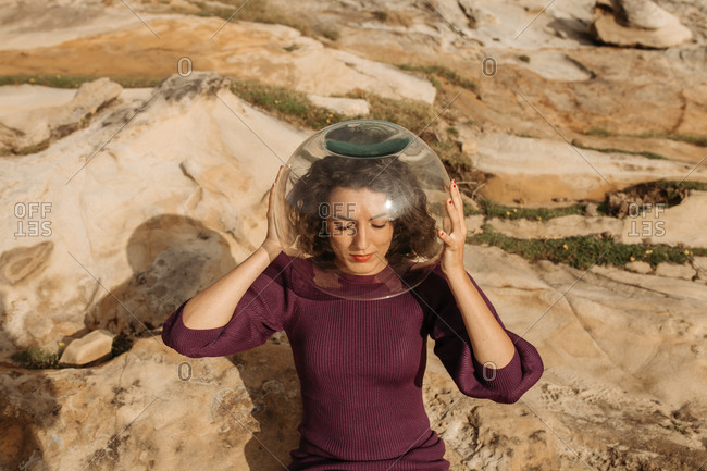 From above female dreaming of being astronaut and sitting in glass helmet on rocky terrain near sea