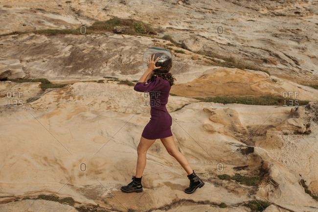Side view of anonymous female dreaming of being astronaut and standing in glass helmet on rocky terrain near sea