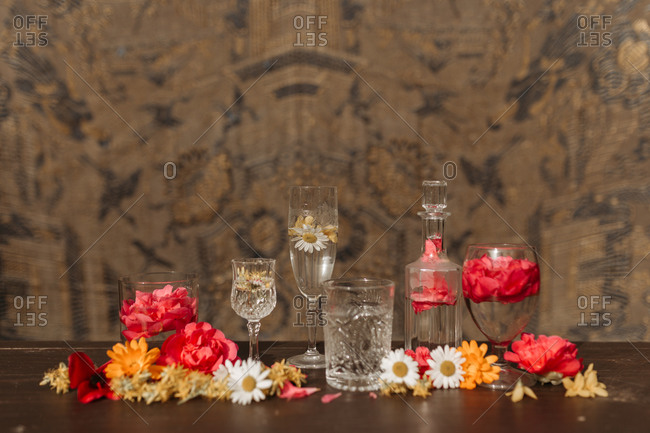 Beautiful stylish arrangement with various types of crystal glasses and bottle placed among assorted fresh flower buds on table against blurred ornamental background