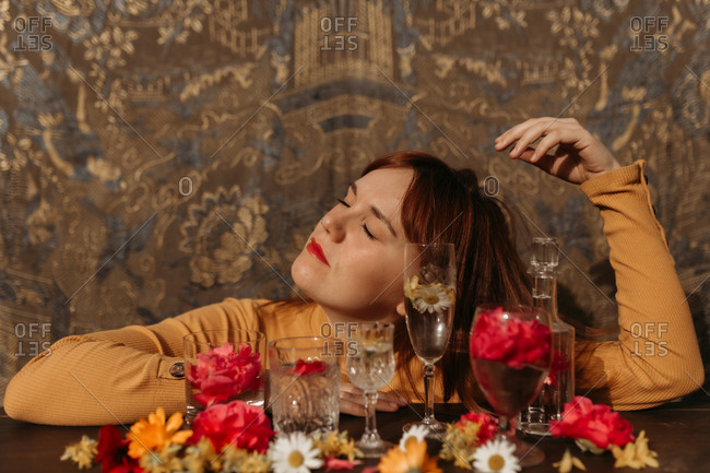 Young sad redhead female holding wineglass while sitting near table with floral and glassware arrangement with eyes closed