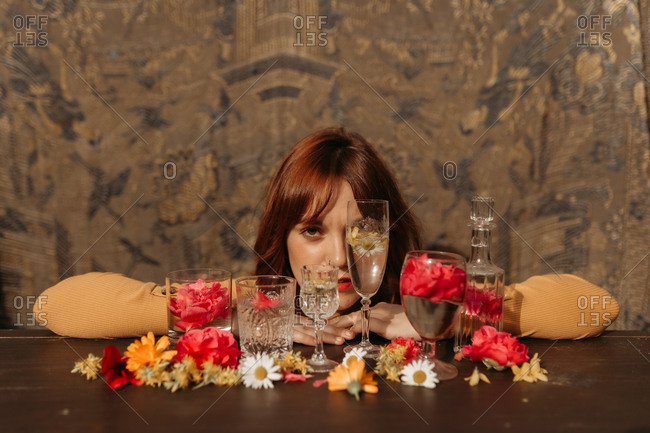 Young sad redhead female with wineglass while sitting near table with floral and glassware arrangement looking at camera