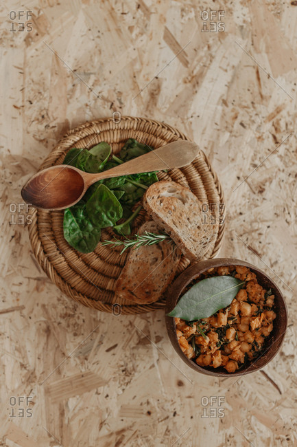 From above of vegetarian chickpea in bowl and slices of bread placed on table with basil for delicious lunch