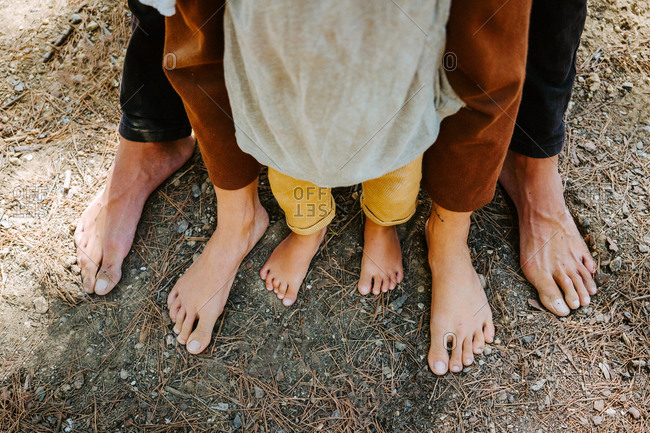From above of barefoot legs of crop family standing together on ground in forest on sunny day