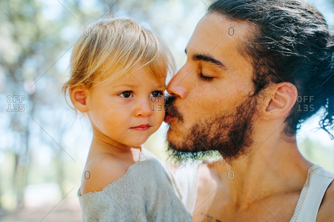 Side view of loving ethnic father gently kissing cute child in cheek while standing in woods together at weekend