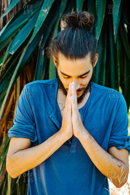 Grateful ethnic male with long hair in bun standing with praying hands with closed eyes and doing yoga in tropical park