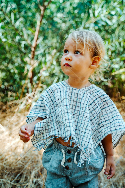 Adorable little child standing in green garden relaxing and looking up