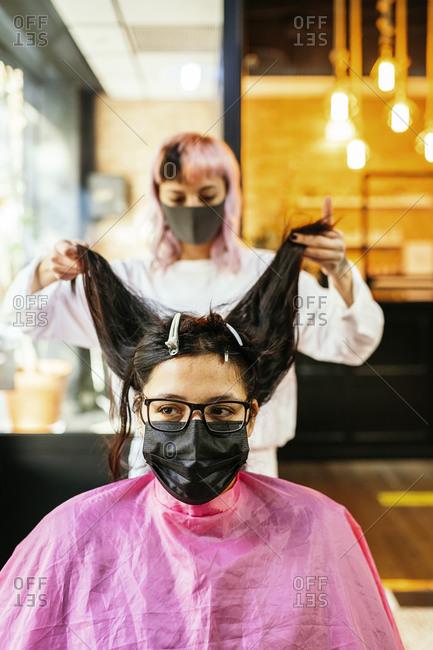 Female hairstylist making hairdo for female client in mask sitting in beauty salon during coronavirus epidemic