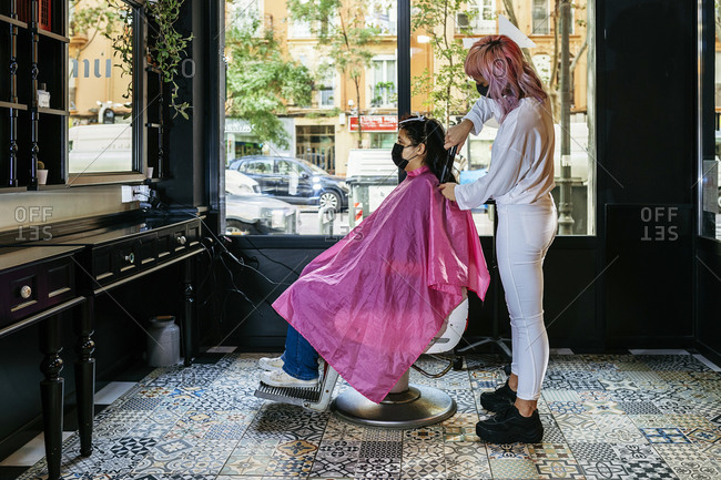 Side view of female hairdresser using curling iron and making trendy hairstyle for client in modern salon during coronavirus pandemic