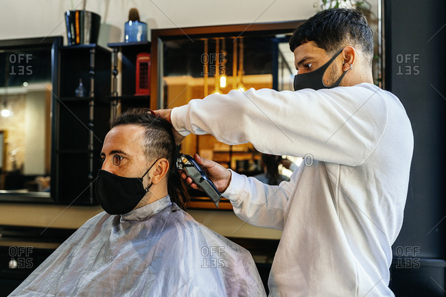 Side view of focused male hairdresser using trimmer and making hairdo for client in modern barbershop