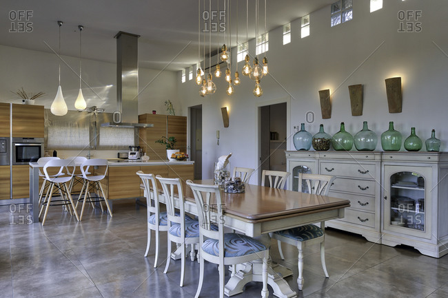 Interior of modern kitchen in apartment with wooden dining table and glowing lamps hanging from ceiling
