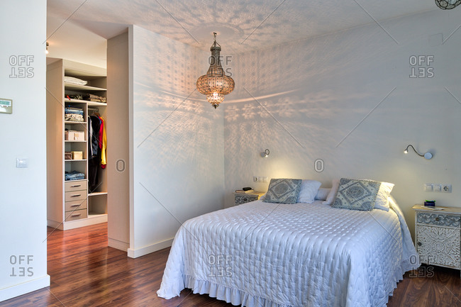 Interior of cozy bedroom with big white bed and classic chandelier hanging from ceiling