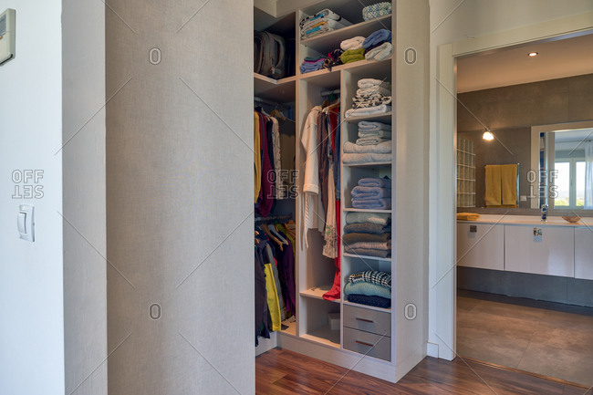Comfortable closet with wooden shelves filled with various colorful clothes in contemporary apartment