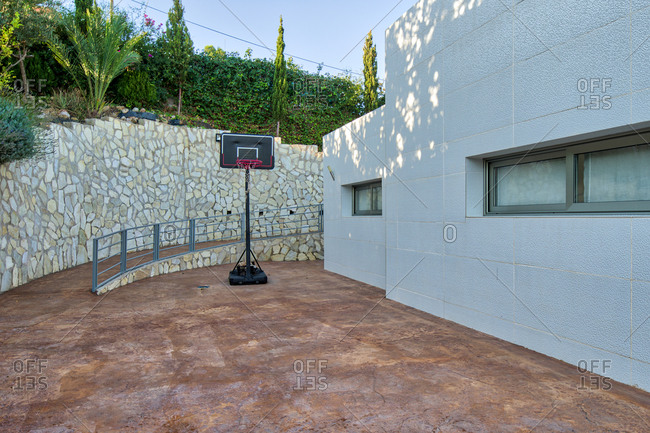 Modern basketball hoop placed in courtyard near contemporary residential building on sunny day