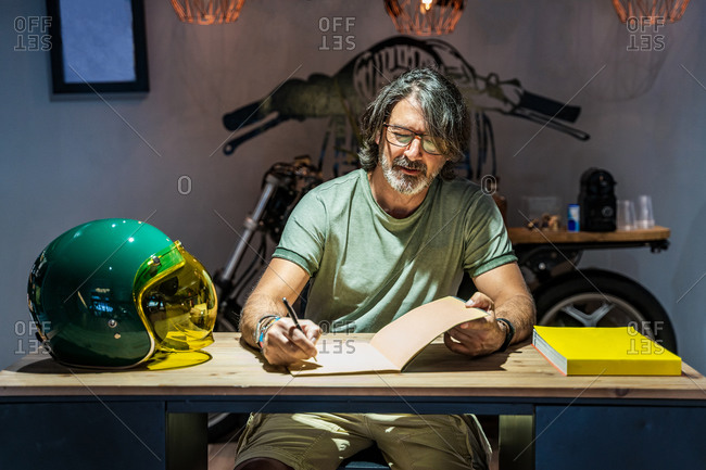 Front view of a man writing in a notebook on a wooden table next to a motorcycle helmet