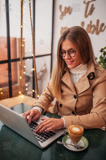 Smiling young female blogger in casual clothes and glasses sitting at table with cup of coffee and typing on laptop keyboard while preparing content for social networks in cozy cafeteria
