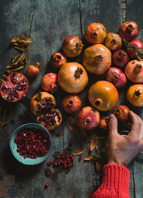 From above unrecognizable hand of person standing at rustic table and putting on ripe fresh pomegranates in pile in dark room