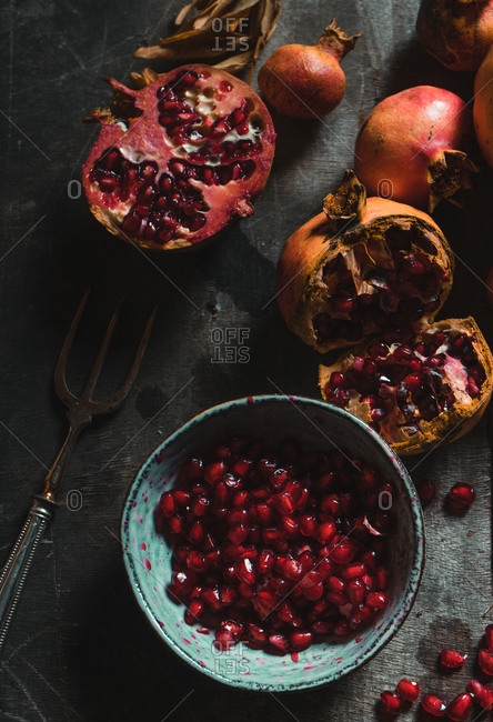 Top view of pile of colorful fresh pomegranates arranged on table with dried plants