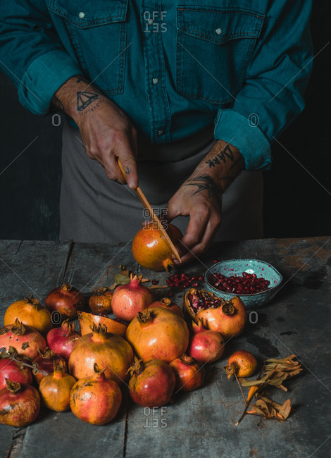High angle of anonymous crop person with knife cutting fresh pomegranate on old wooden table in rustic kitchen
