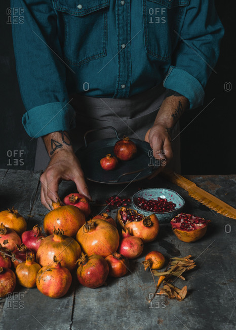 Unrecognizable tattoo hand of person standing at rustic table and putting on ripe fresh pomegranates in pile in dark room
