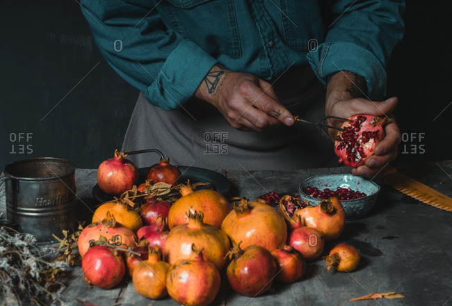 Unrecognizable crop person standing at table in rustic kitchen and peeling fresh delicious pomegranate with fork