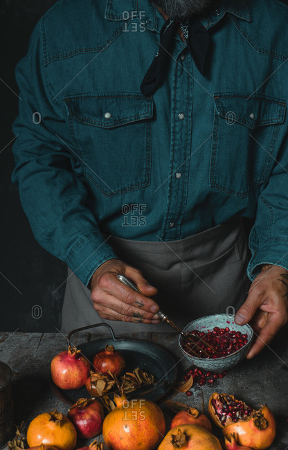 Unrecognizable crop tattoo hands of person standing at table in rustic kitchen and peeling fresh delicious pomegranate with fork