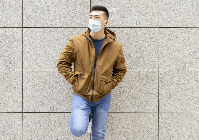 Serious young Asian male student in casual outfit and medical mask for coronavirus prevention standing against gray stone wall and looking away