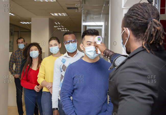 Group of multiracial colleagues in casual clothes and medical masks passing through procedure of body temperature control for coronavirus prevention before entering workplace