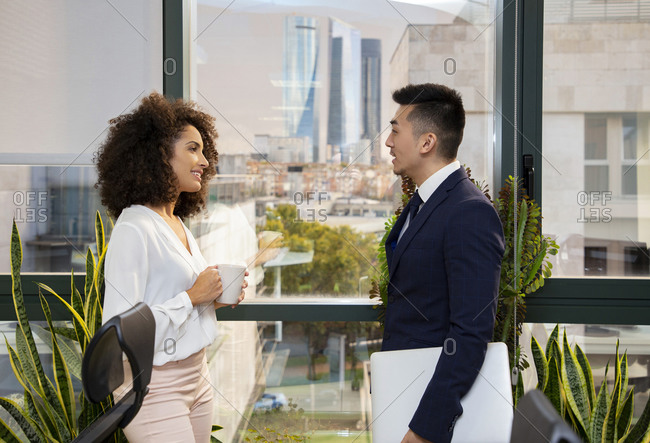 Side view of positive young African American woman with cup of coffee and Asian male colleague with laptop standing near window and discussing news while working together in modern office