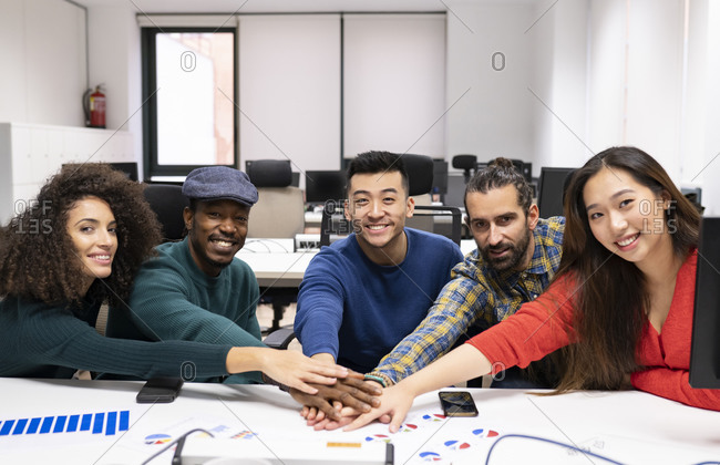 Young multiracial successful startup team gathering around table with diagrams and stacking hands together while discussing business strategy in modern office