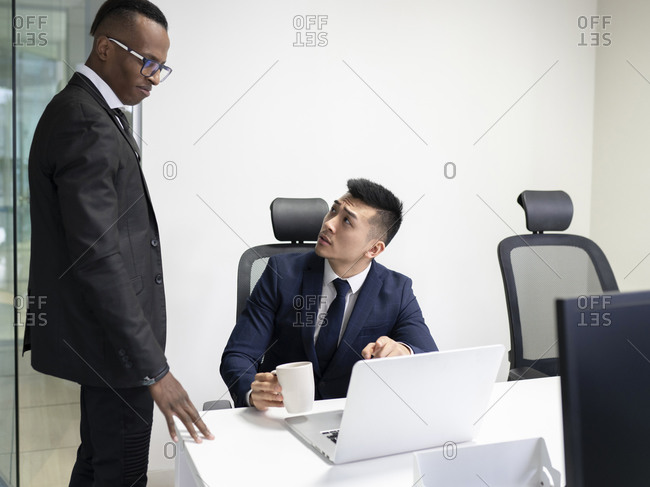 Serious young Asian male boss in formal suit with cup of coffee pointing at laptop screen and asking African American manager to explain problem solution during meeting in office
