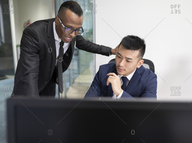 Serious young Asian male boss in formal suit looking at laptop screen with African American manager to explain problem solution during meeting in office