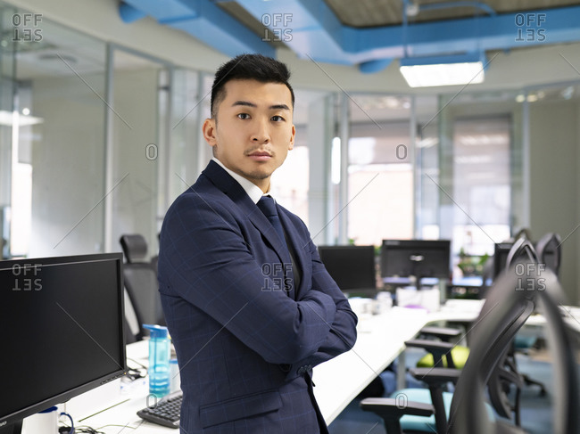 Side view of serious young Asian male manager in formal suit looking at camera while standing near table with computers in contemporary coworking office