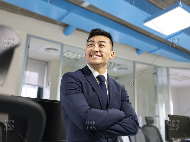 Cheerful young Asian male manager in formal suit looking away while standing near table with computers in contemporary coworking office