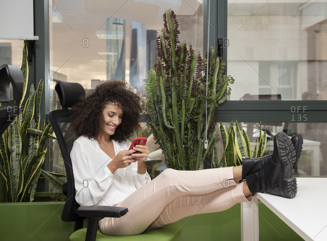 Full body side view of positive young female employee in casual outfit sitting on chair with legs on table and messaging on smartphone while resting during break in modern workspace